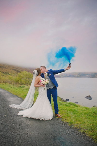 Bride and groom kiss with blue smoke bomb