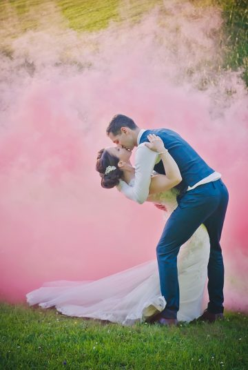 Couple embrace with pink smoke bombs in the background
