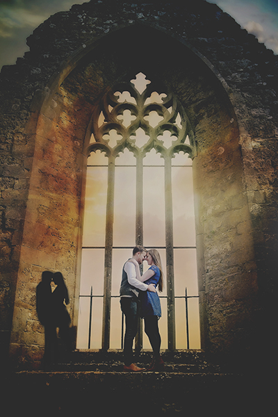 Newly engaged couple at sunset in old abbey